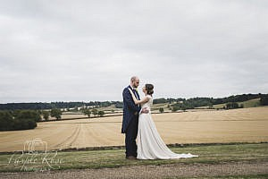 Bride and groom standing in front of an open field