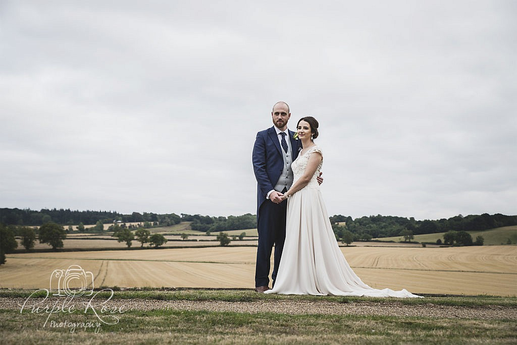 Bride and groom with open fields behind them