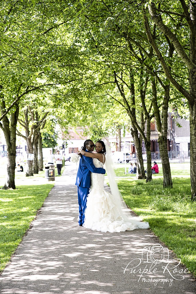 Bride and groom embracing in a tree lined path