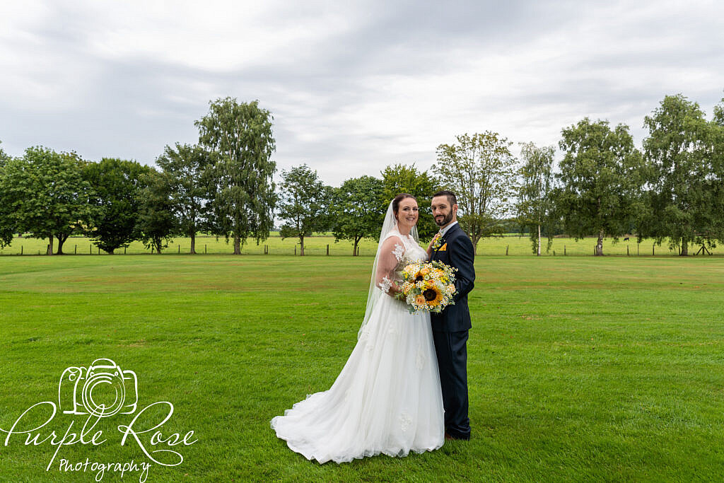 bride and groom standing by a golf course