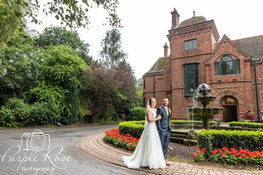 Bride and groom in front of a manor house