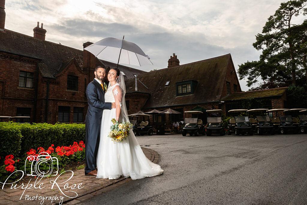 Bride and groom sheltering under an umbrella