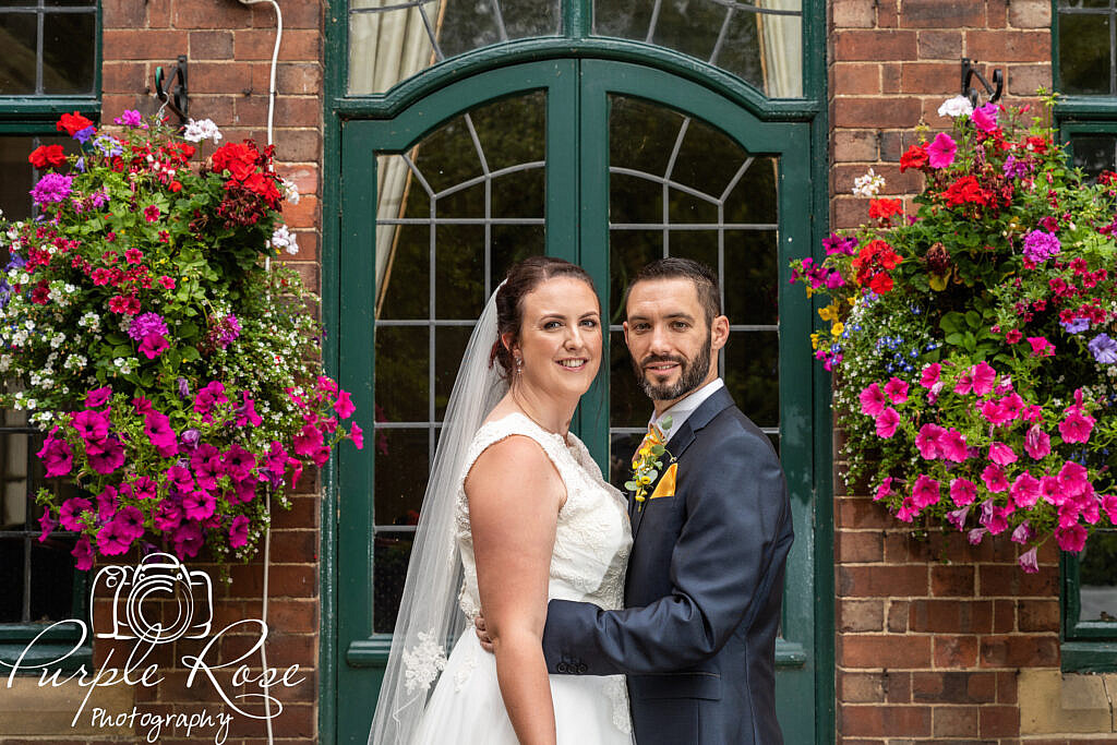 Bride and groom surrounded by hanging baskets
