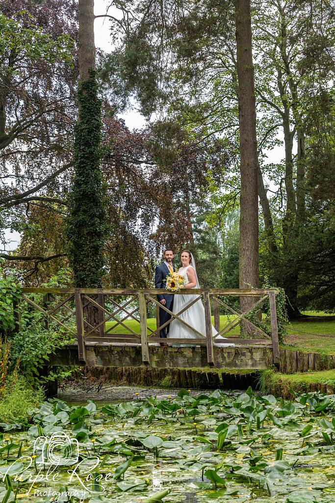 bride and groom on a wooden bridge