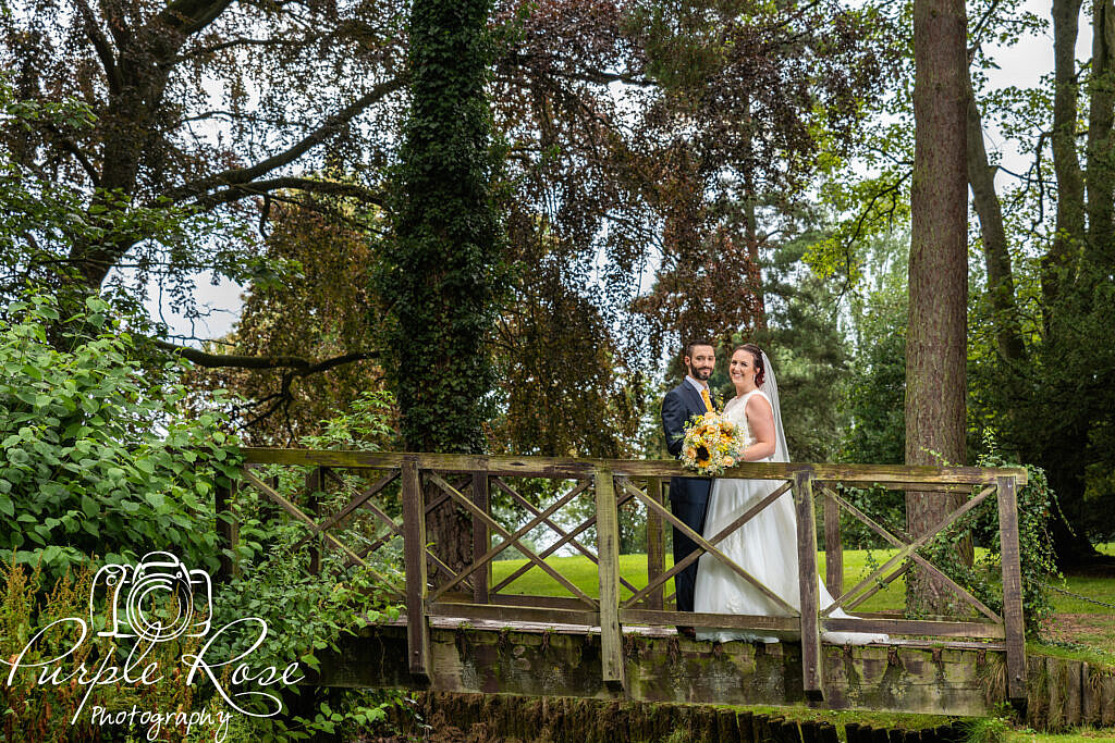 Bride and groom standing on a wooden bridge