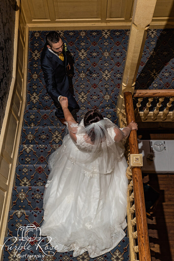 Bride and groom walking down a staircase