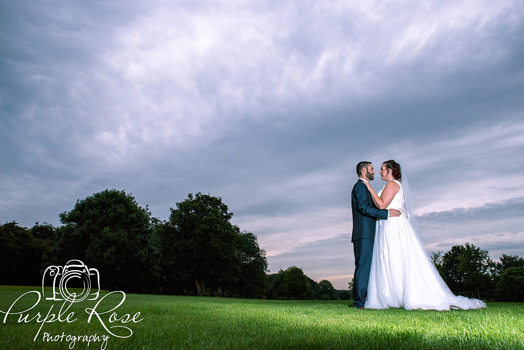 bride and groom in front of a dark stormy sky