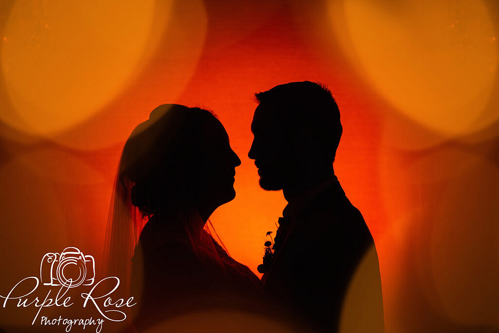 Orange background silhouette of bride and groom