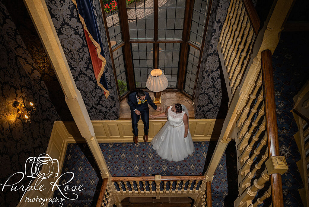 Bride and groom waiting on a staircase