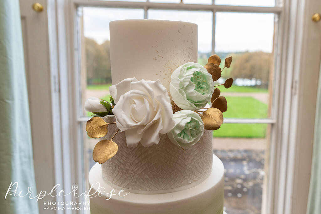 Gold, green and white flowers and foliage on a wedding cake in Kelmarsh Hall Northampton