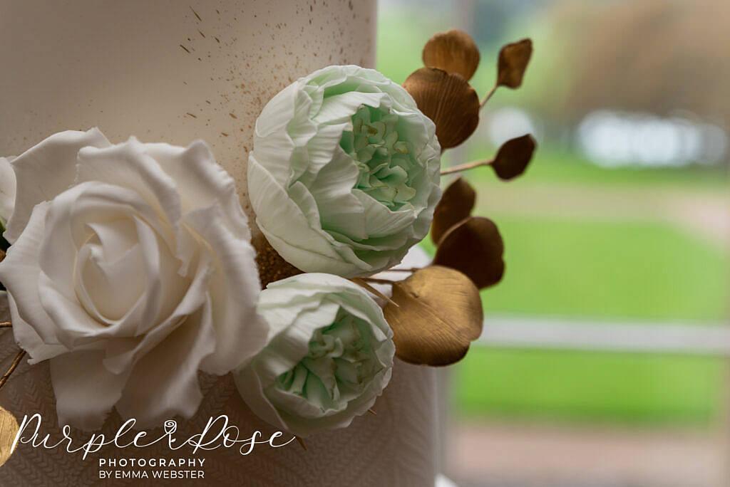 Intricate hand made flowers on a wedding cake in Kelmarsh Hall Northampton