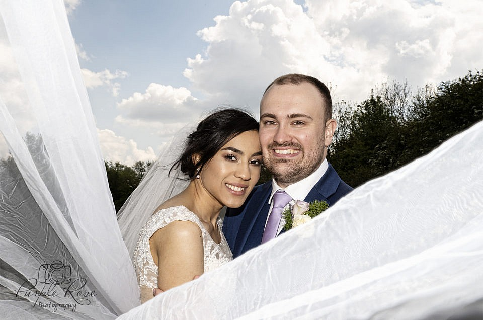 Bride and groom wrapped in brides wedding veil