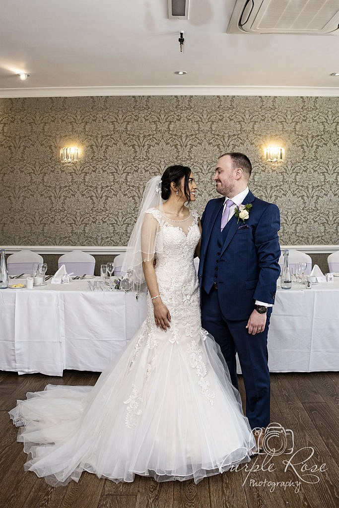 Bride and groom standing in their wedding reception room