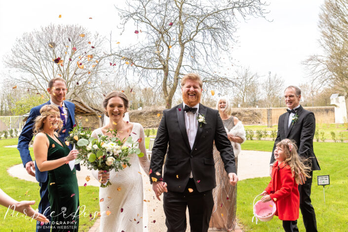 Bride and groom laughing as confetti is thrown around them