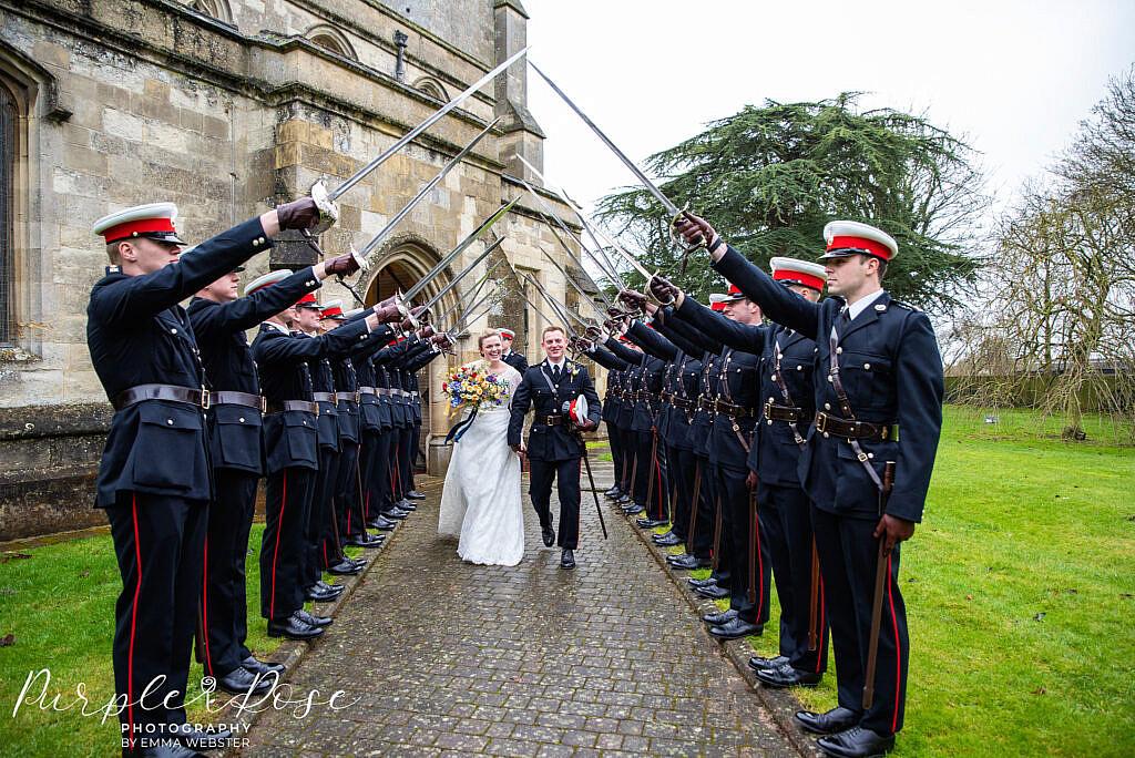 Bride and groom walking under swords