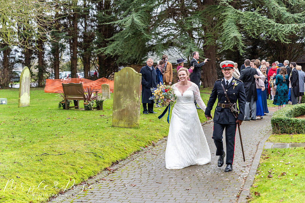 Bride and groom walking from the church