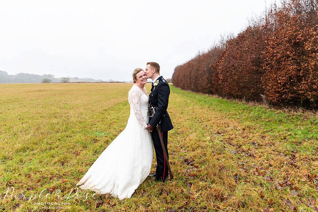 Groom kissing his bride in a field