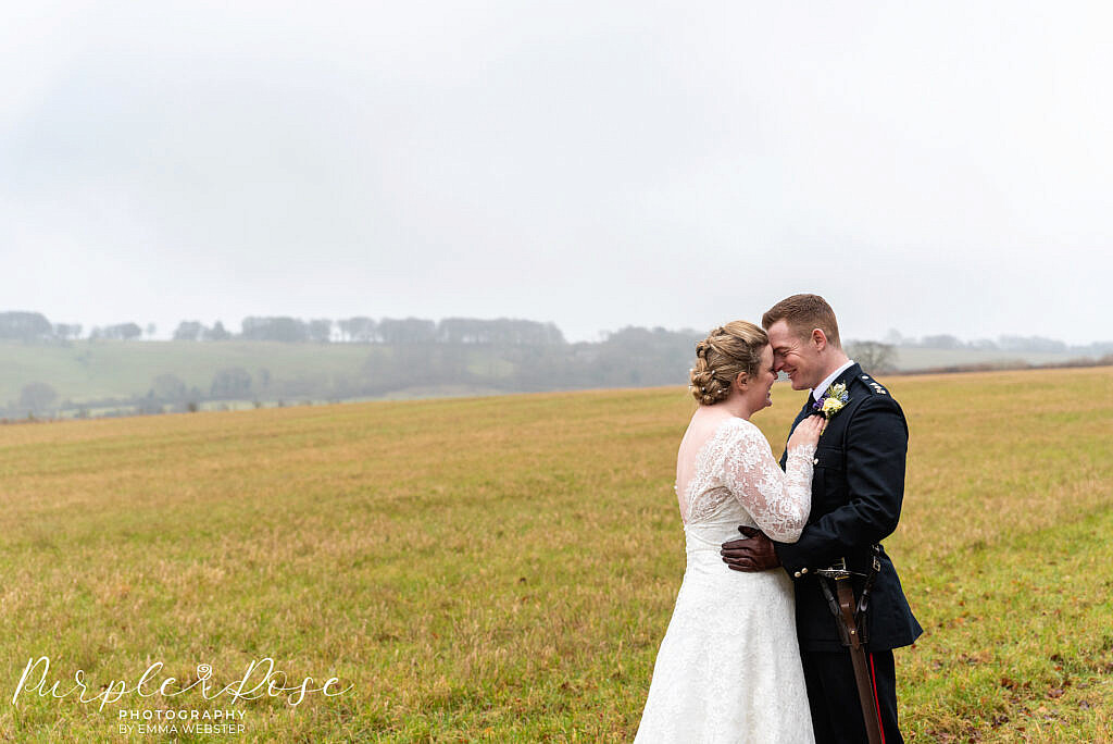 Bride and groom embracing in a field