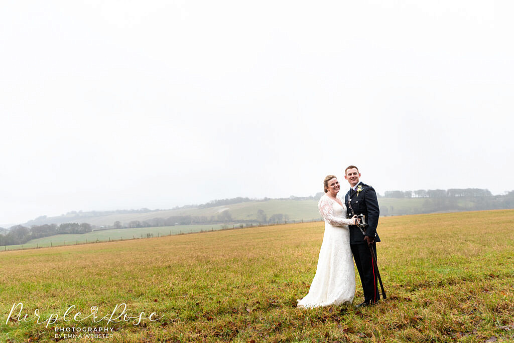 bride and groom in a field on their wedding day