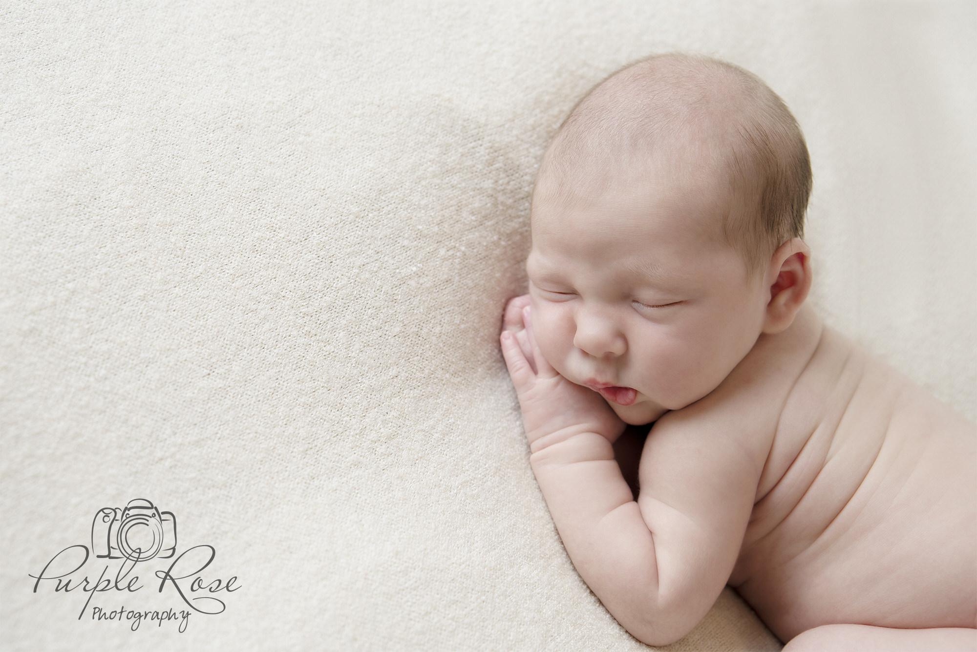 Baby sleeping on cream blanket