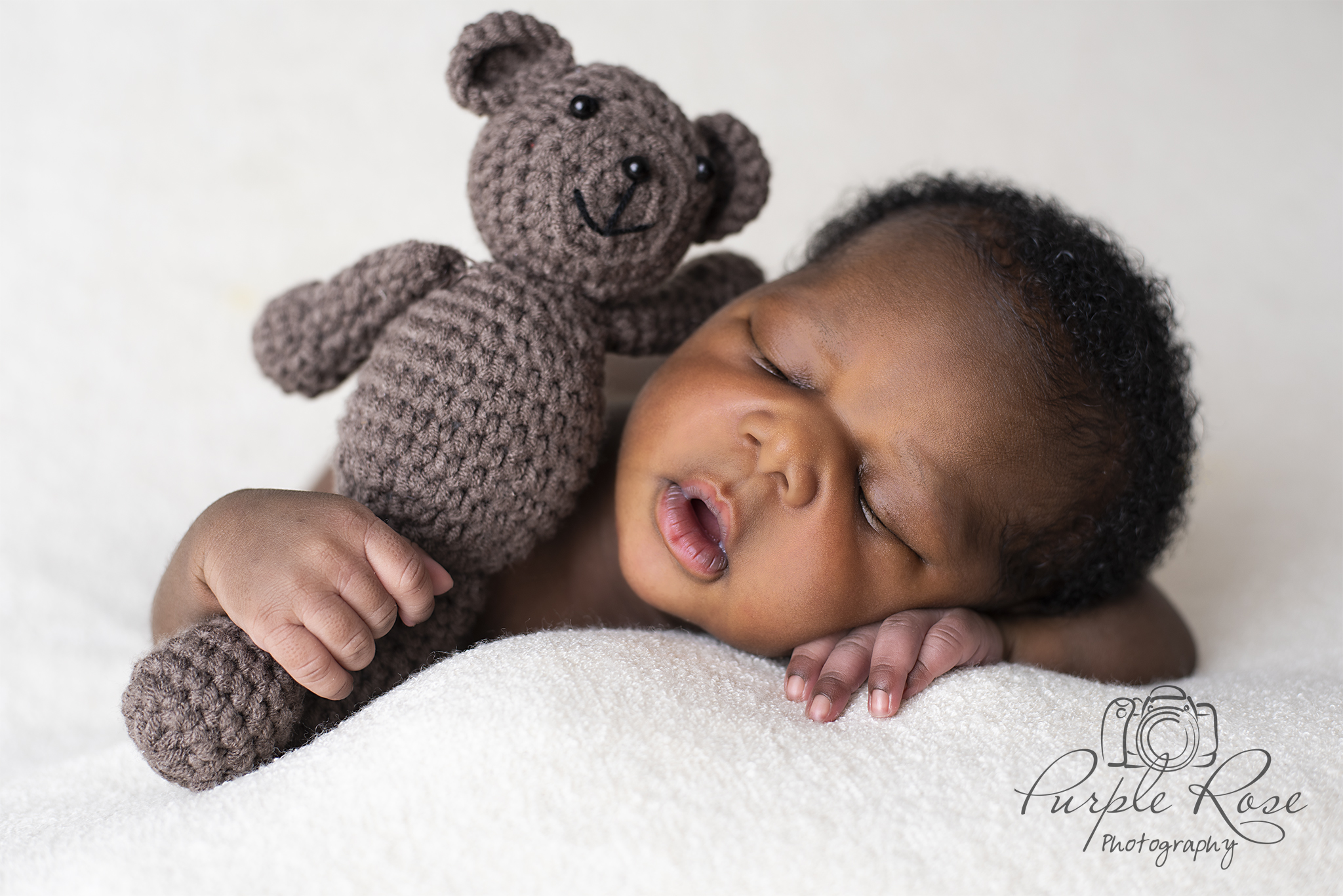 Baby sleeping while holding a teddy