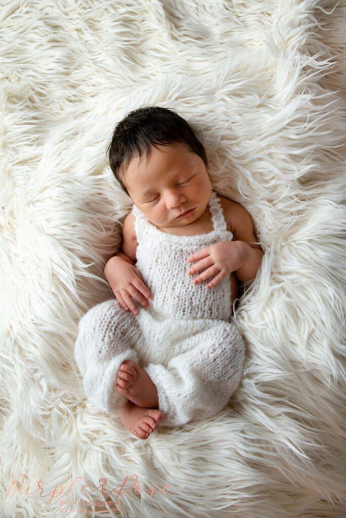 New born baby sleeping of fur layers