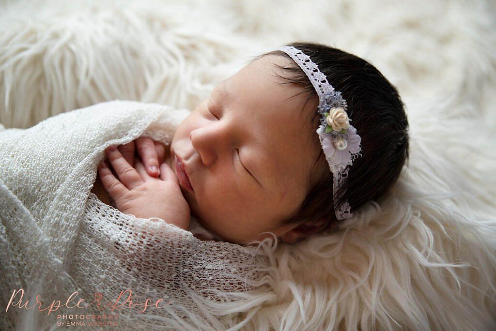 New born baby asleep in a wrap