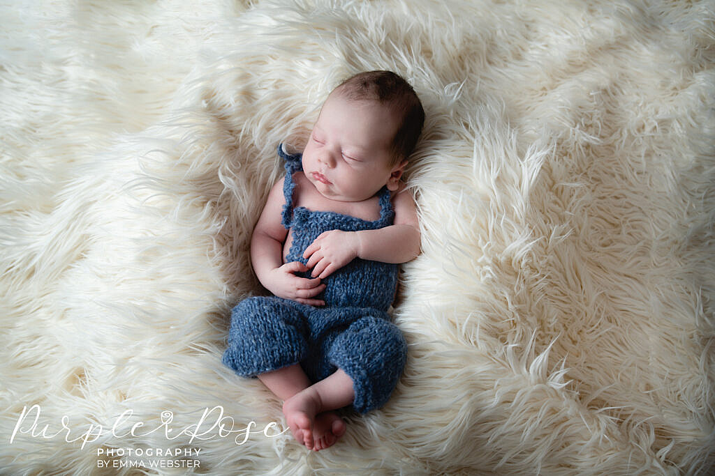 Baby sleeping in a blue romper