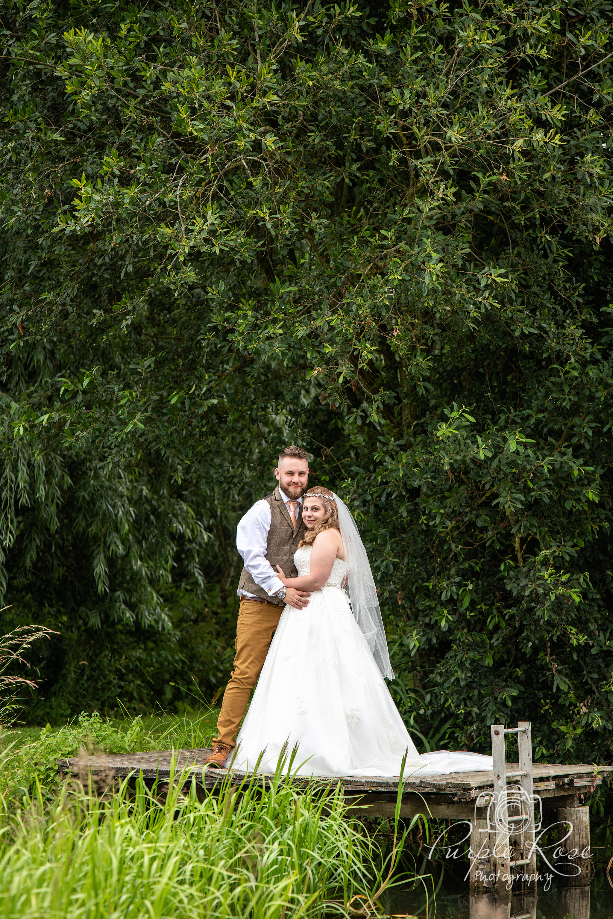 Bride and Groom standing on a fishing jetty