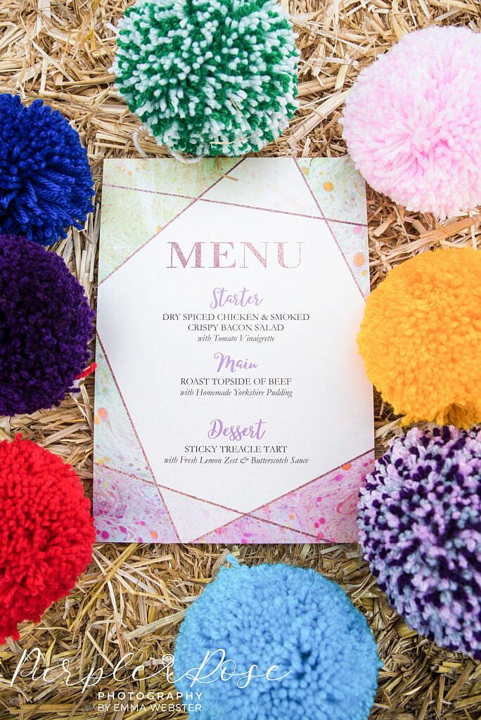 Wedding menu surrounded by pom poms