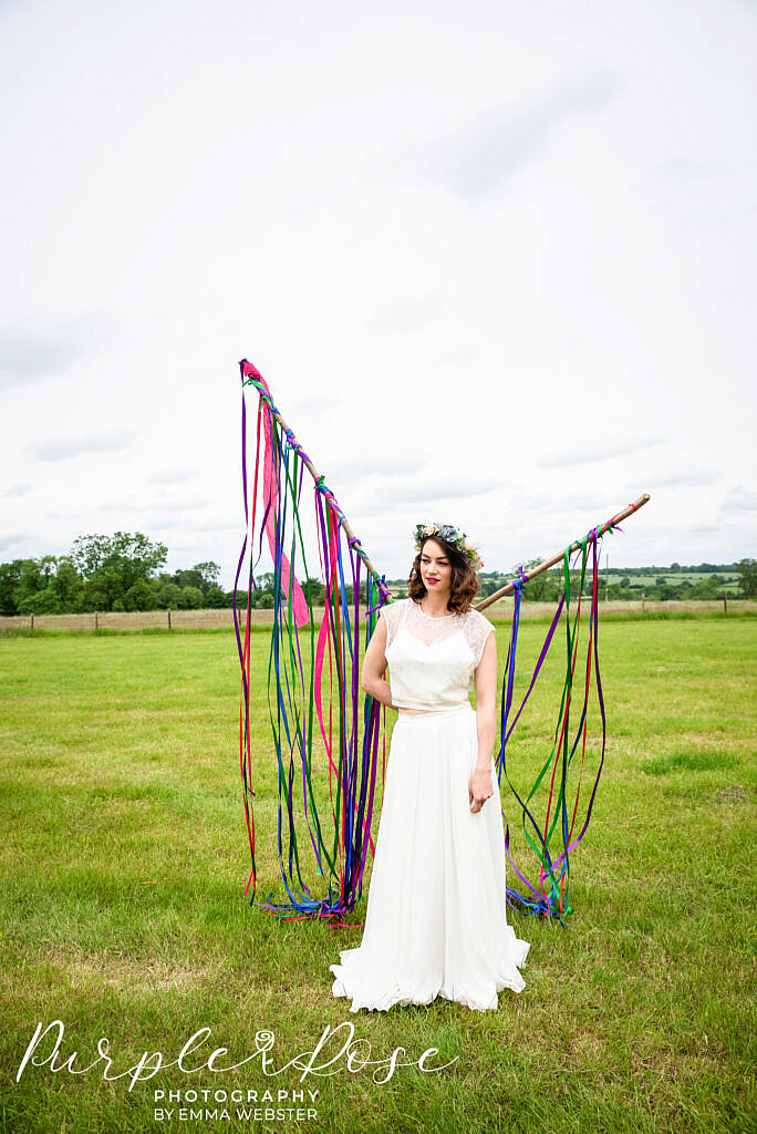 bride standing in front of ribbons in a field