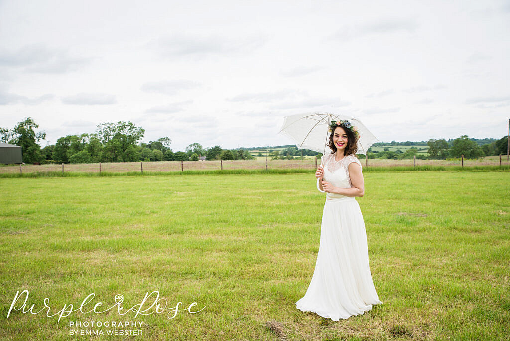 bride standing in a field with an umbrella