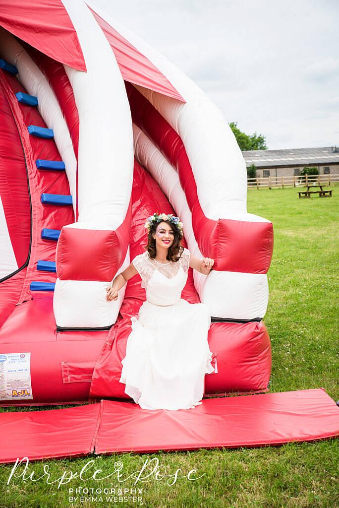 Bride sliding down a bouncy castle