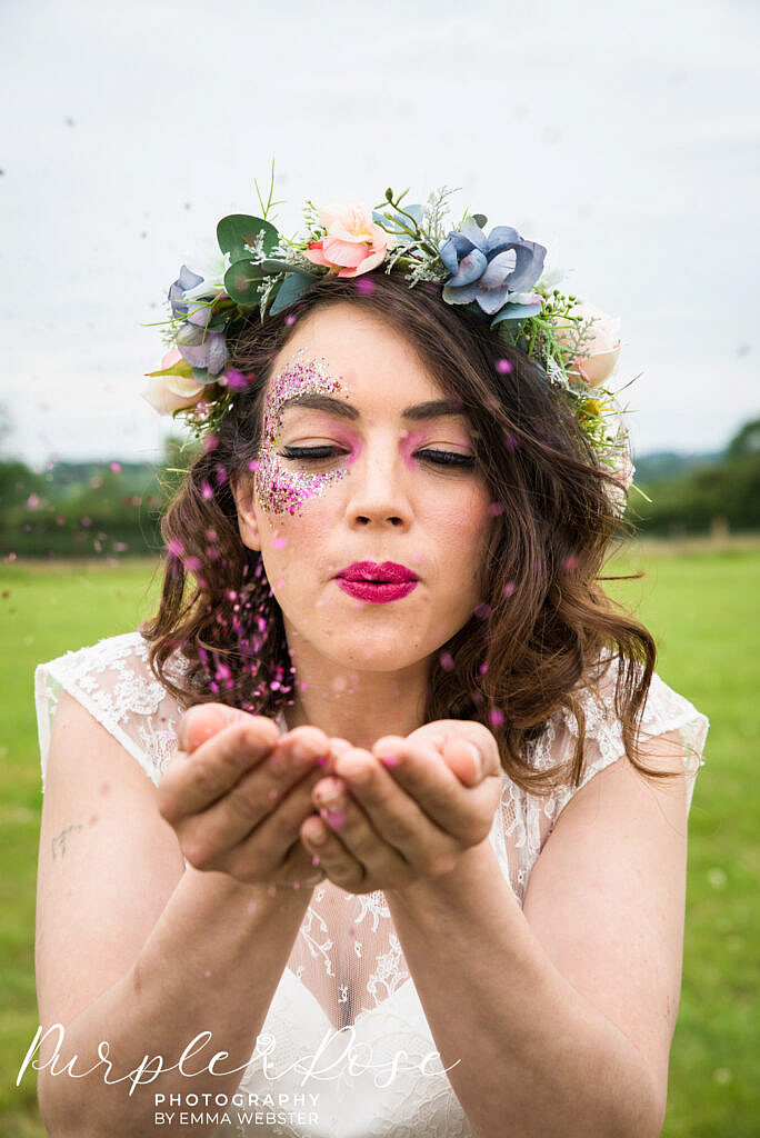 bride blowing glitter from her hands