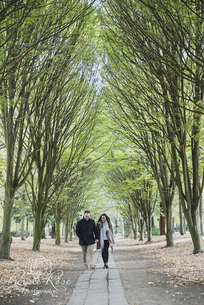 Couple walking along a tree lined path