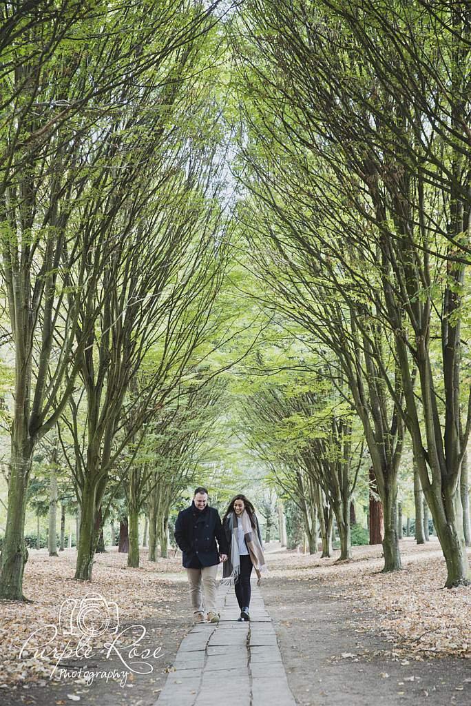 Couple walking along a tree lined path