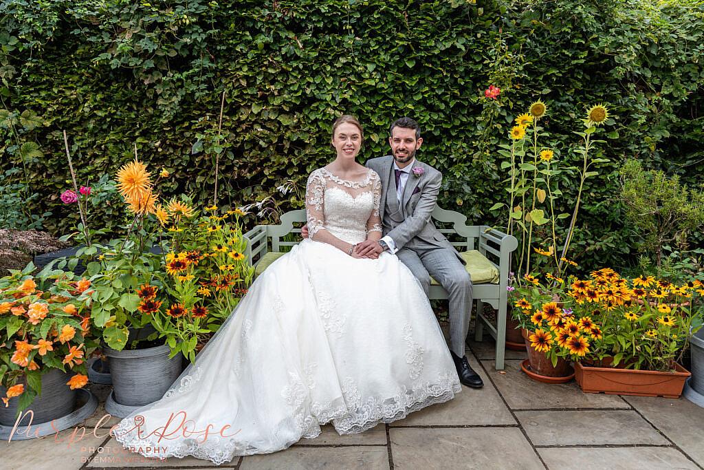 Couple sat in garden of flowers