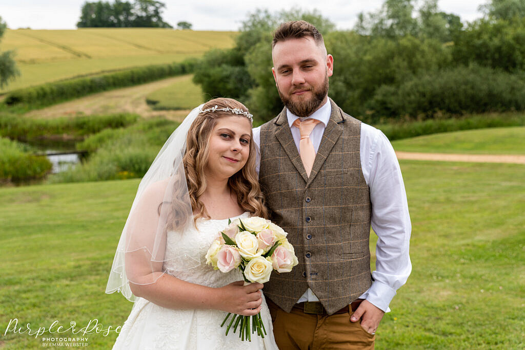 Bride and groom in front of rolling fields