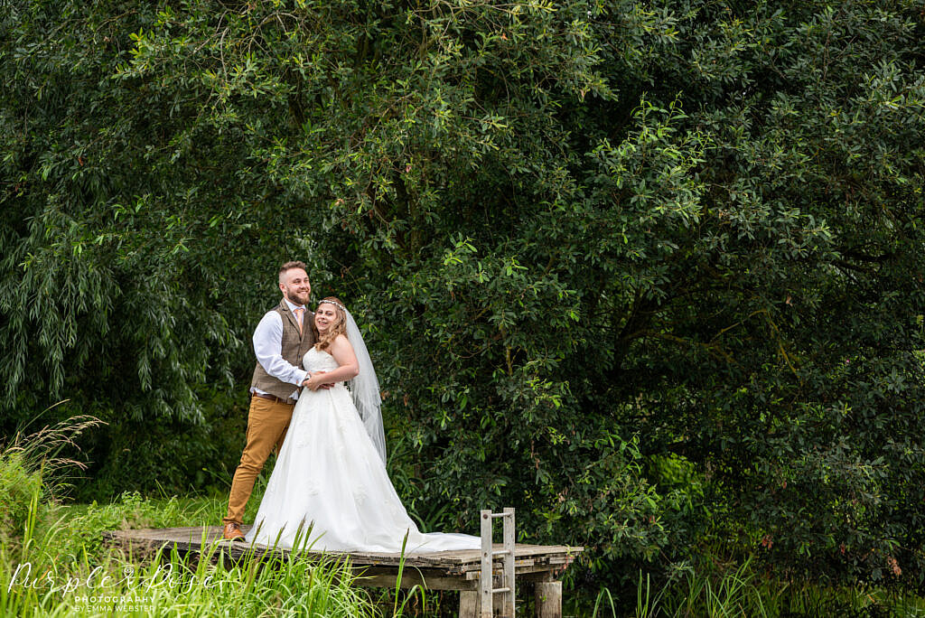 Bride and groom standing together by a lake