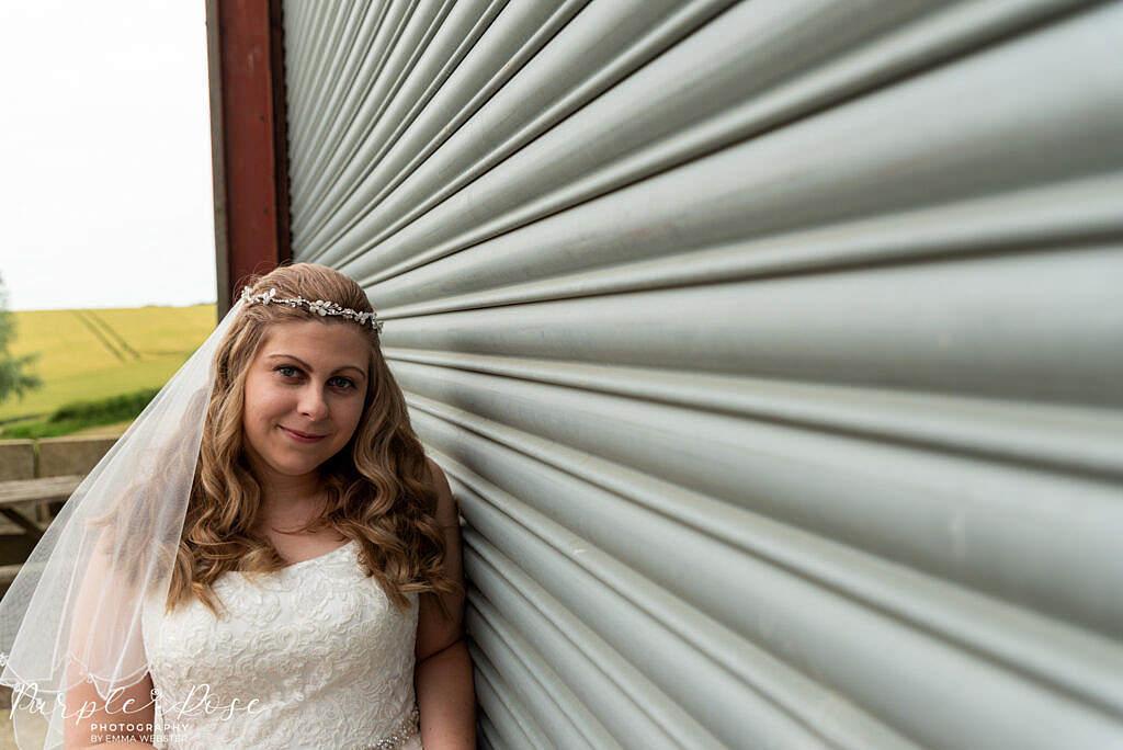 bride leaning on metal barn door