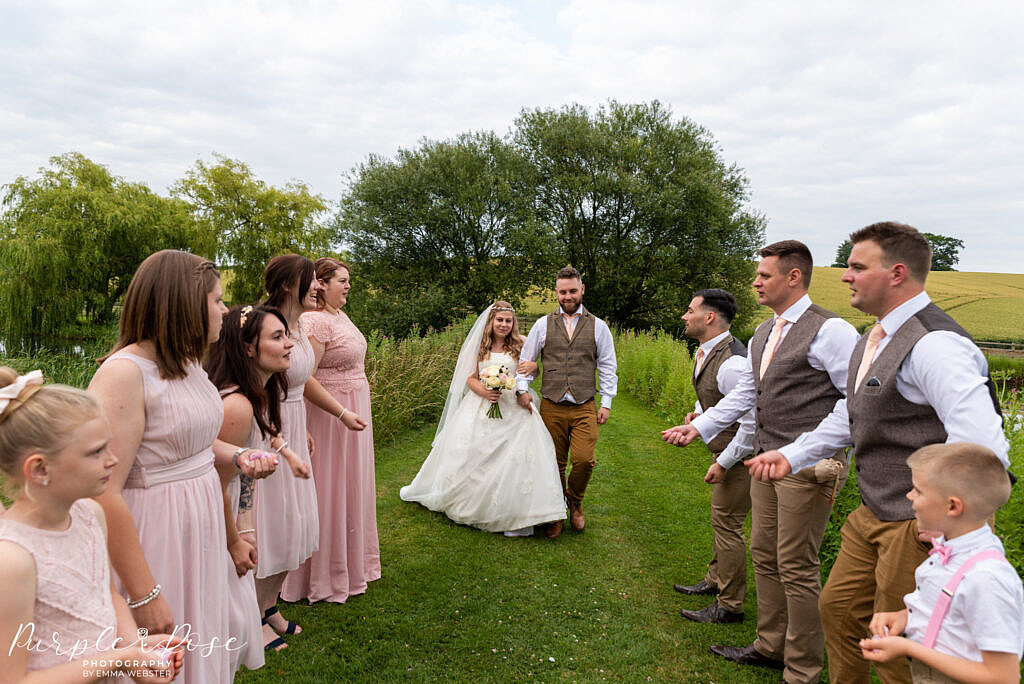 bride and groom surrounded by wedding party