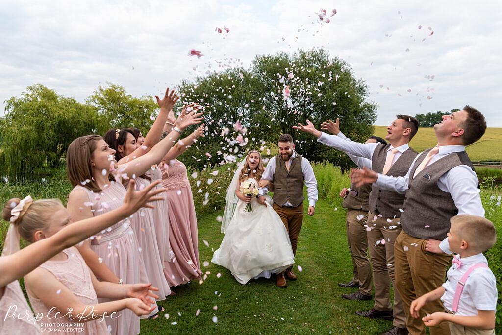 Bride and groom walking through confetti