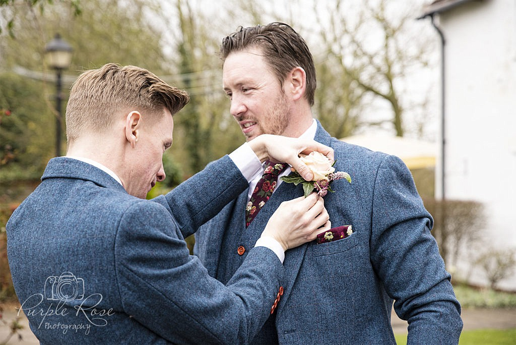 Best man pinning the Grooms button hole