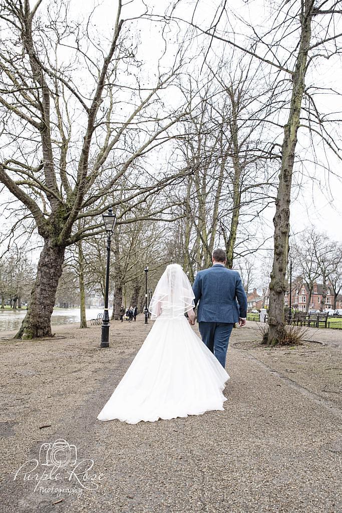 Bride and groom walking besides Bedford River Bank