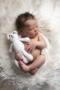 Sleeping baby holding a teddy