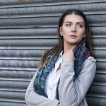 Portrait of woman leaning against shutters
