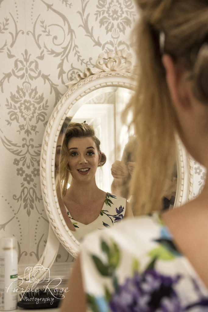 Bridesmaid looking in the mirror while her hair is being styled.