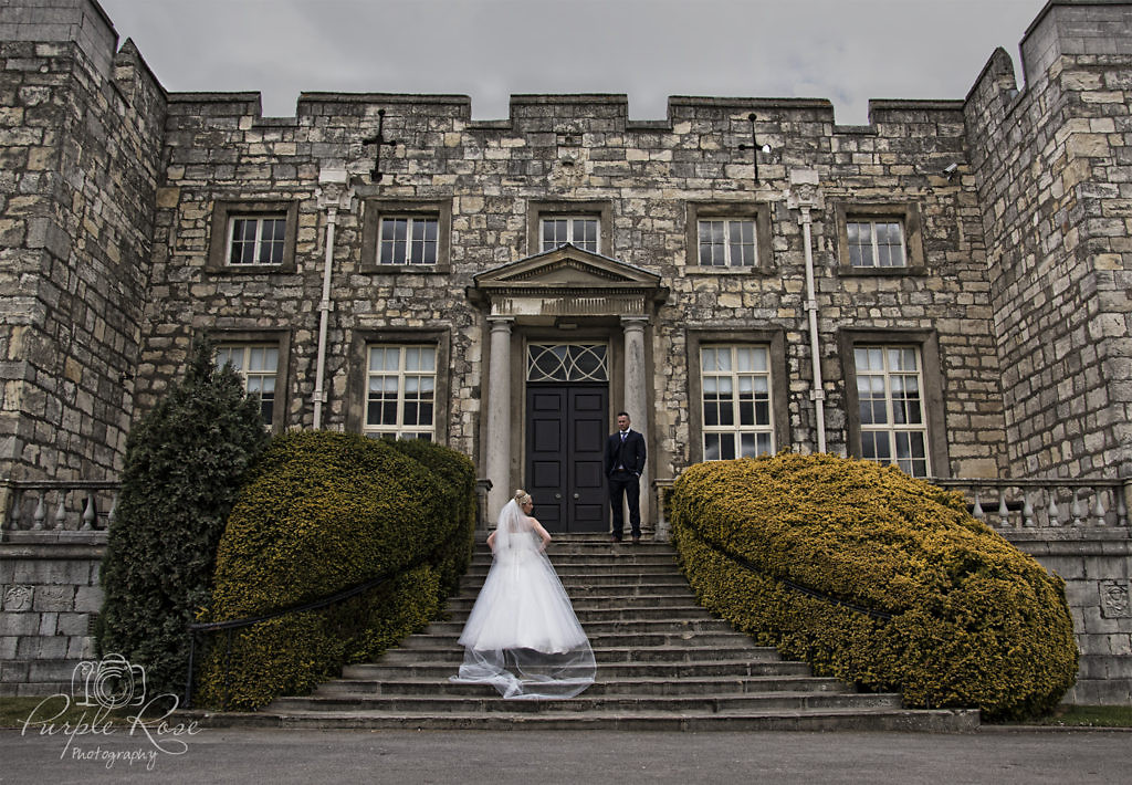 Bride and groom standing on steps outside their venue