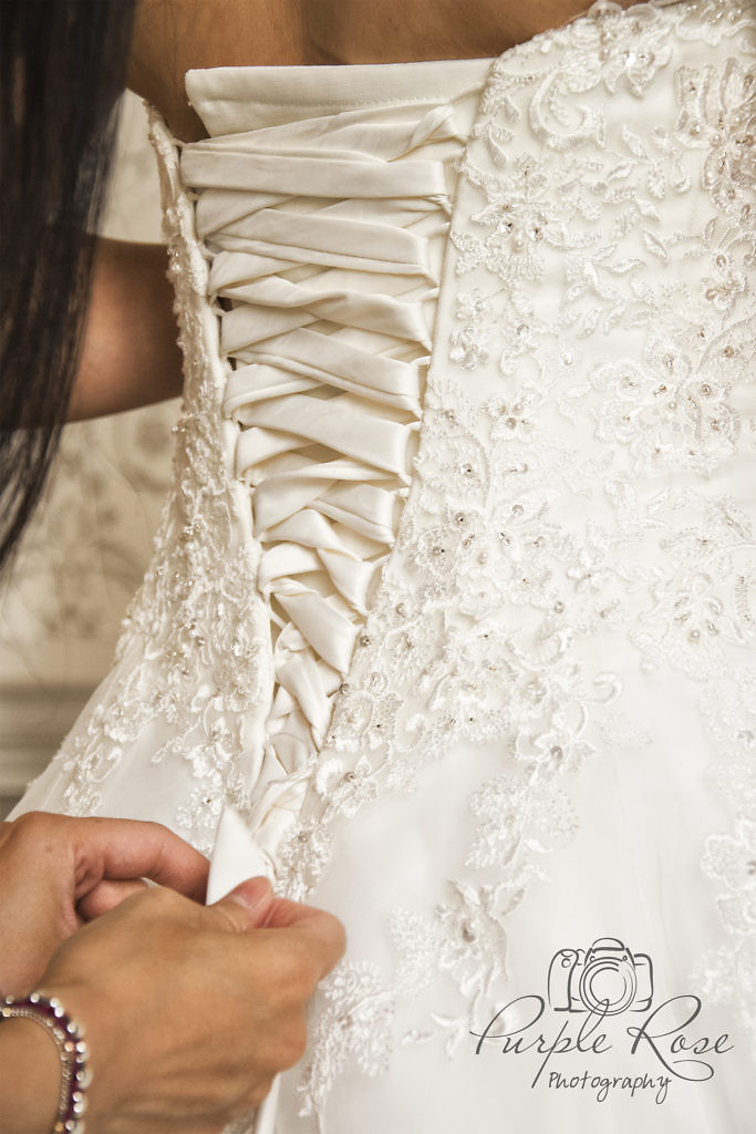 Bridesmaid lacing up the brides dress.