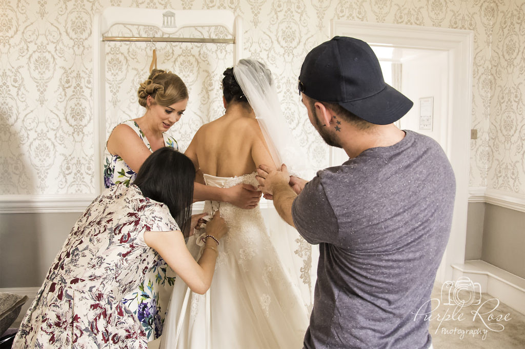 Freinds and family helping the bride get into her dress.